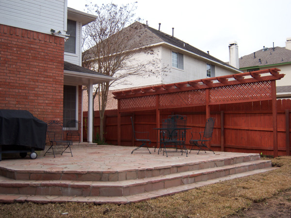 Flagstone patio with steps and a pergola privacy wall