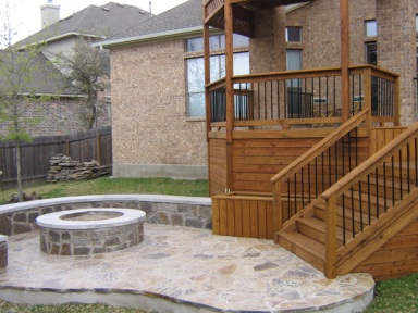 Flagstone patio with fire pit, bench retaining wall and adjoining deck