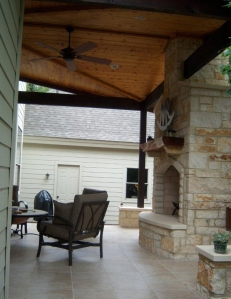 Covered patio with custom outdoor limestone fireplace in Austin
