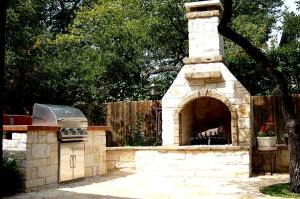 Natural stone patio and outdoor fireplace by Archadeck of Austin